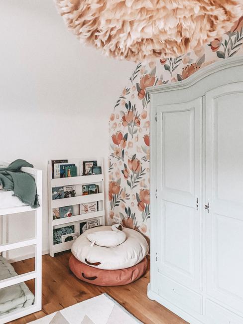Fragment pokoju dziecięcego z białą szafą, poduszkami w kształcie łabędzie, półek oraz tapety na ścianie
