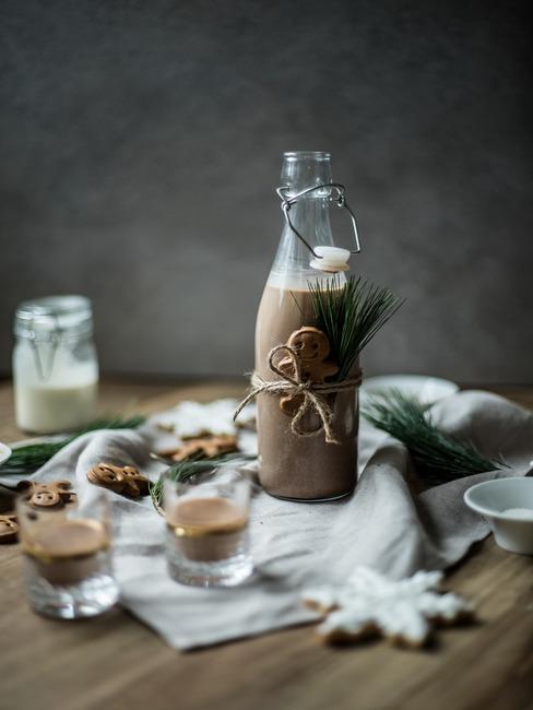 Szklana butelka z domowym likierem przewiązana świątecznym pierniczkiem