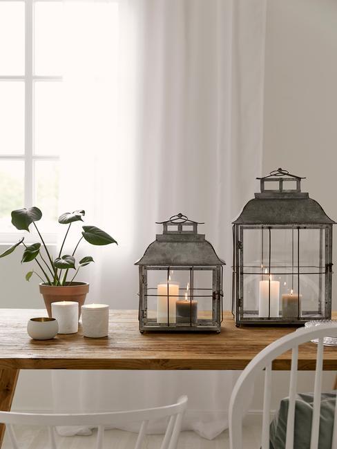 Drewniany stół z rośliną w doniczce oraz dwoma latarenkami