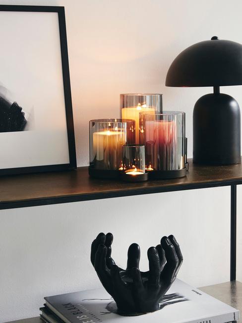 Zbliżenie na czarną półkę ze świeczkami w czarnych świecznikach