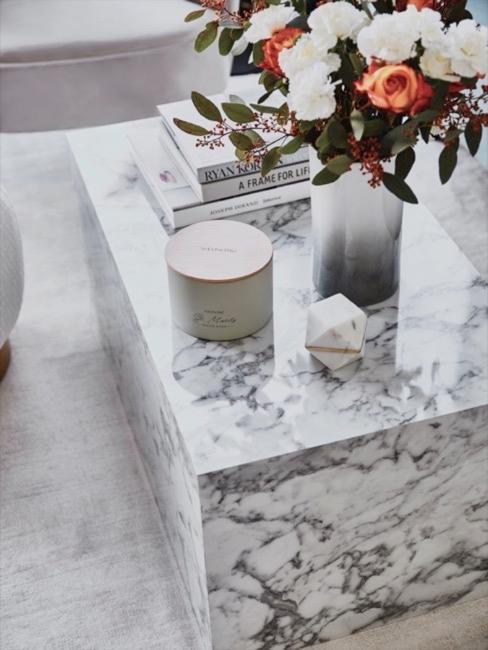 Marmeren kubus witgrijs gedecoreerd met bloemenboeket, tafelboeken en kaarsen.