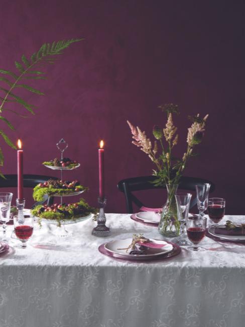mesa de boda blanca con decoración lila y una pared de color púrpura