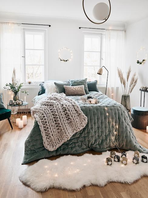 Bed met saliegroene plaid en kussen versierd met beige deken en pampagras