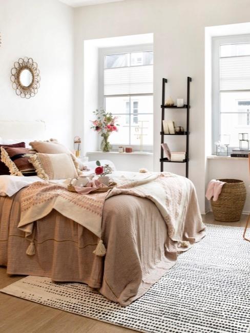 Praktische ingerichte studio met bed, klein bureau en planken met opbergruimte