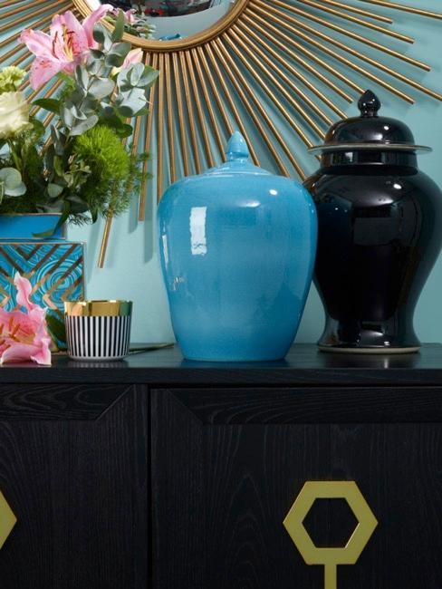 Cómoda con decoraciones asiáticas, tibores en color azul y negro y jarrón azul con flores