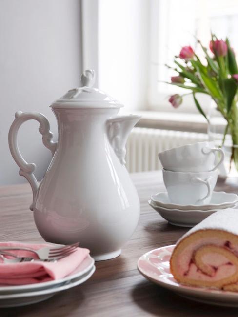 Set de tetera y tazas blanco sobre mesa de madera con tulipanes de fondo