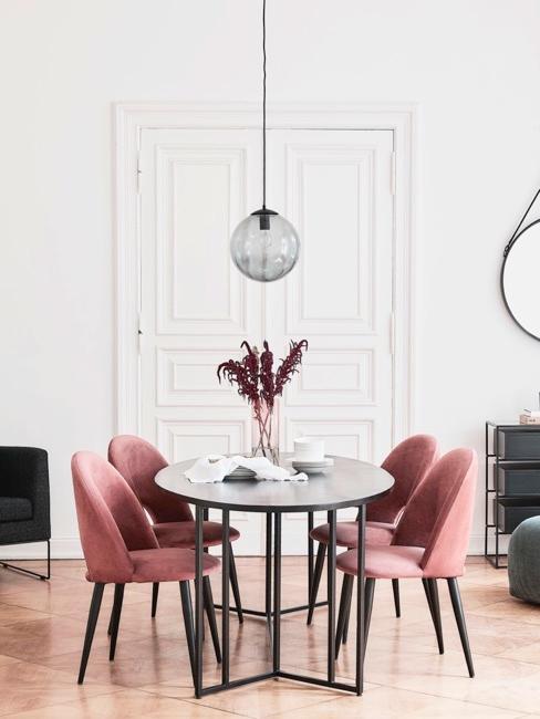 Jadalnia w starym budownictwie z różowymi krzesłami oraz metalicznym stołem