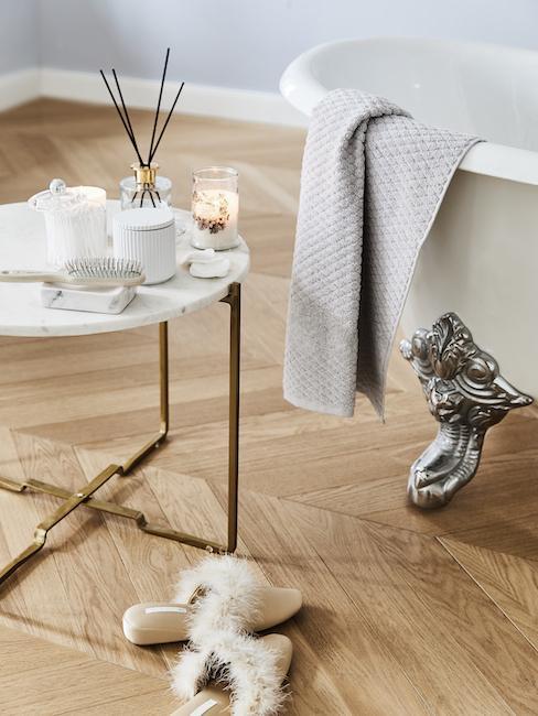 Łazienka z wanną, szarym ręcznikiem oraz białym stolikiem z matelicznymi nogami