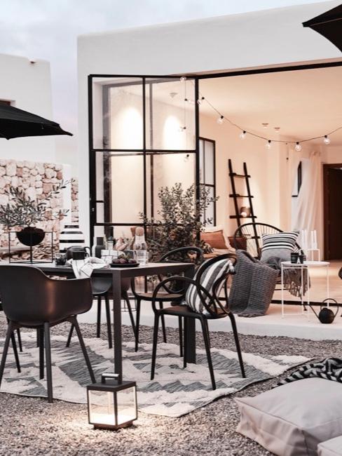Terras inrichten in zwart-wit met zwart outdoor meubilair, zwarte parasols en licht textiel