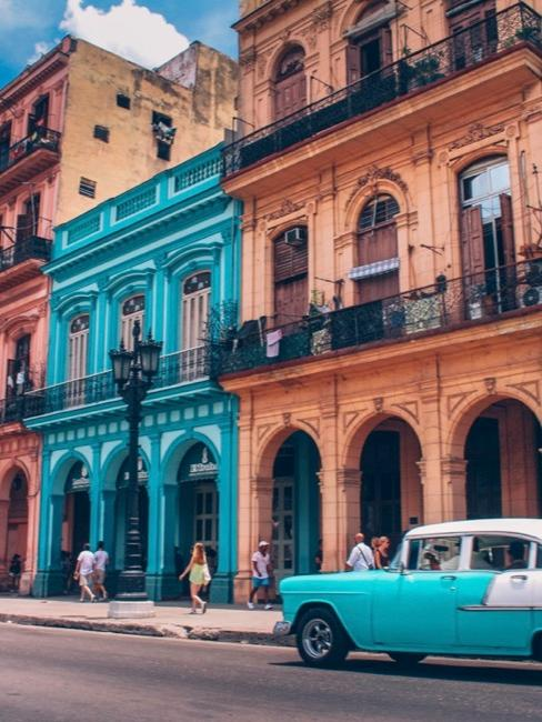 Blauwe auto voor kleurrijke huizen in Cuba