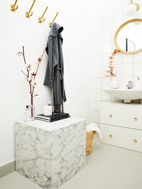 Weißes Bad ohne Fenster, Waschbecken mit Holzspiegel und einem Unterschrank, sowie ein Beistelltisch in Marmor-Optik in Weiß unter einer Garderobe