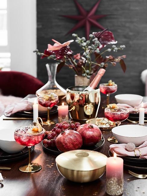 Zastawiony czarny stół, szklankami do drinków oraz dekoracjami imprezowymi