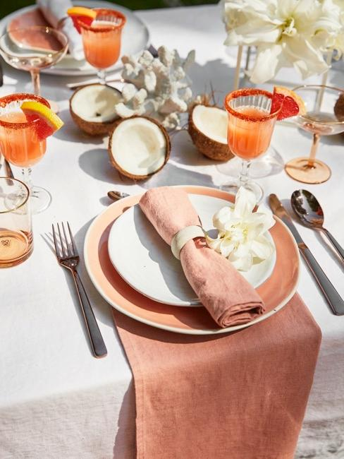 una mesa con vajilla y decoración veraniega, con servilletas de color melocotón