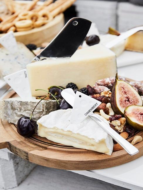 tabla pequeña de madera con quesos y frutas frescas
