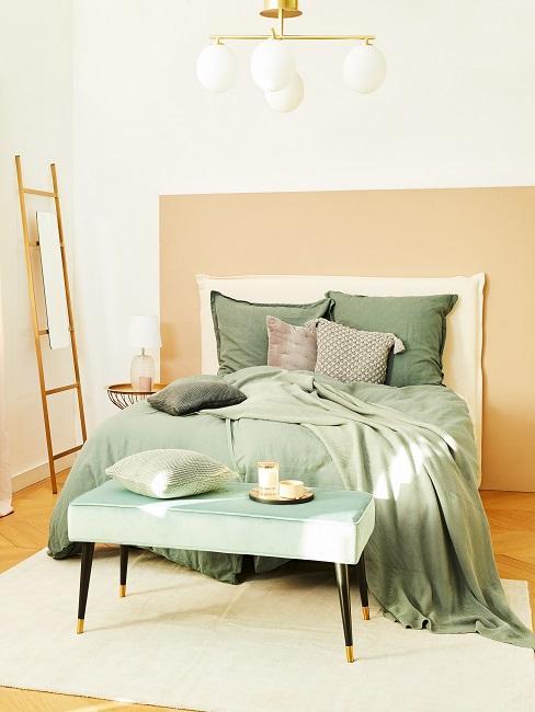 Schlafzimmer mit grüner Bettwäsche und einer grünen Bettbank vor dem Bett
