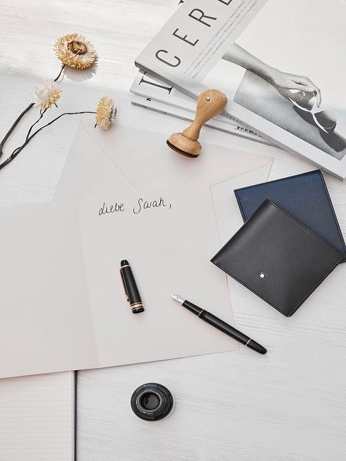 Ansichtkaart met open pen op een bureau, daarnaast tijdschriften, een postzegel en nog veel meer