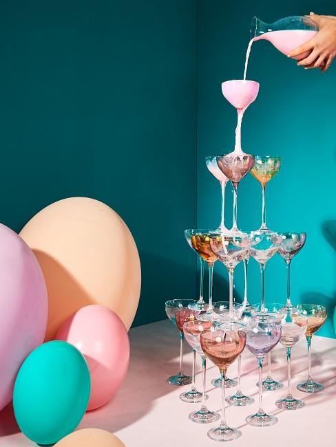 Dekoracja stołu urodzinowego z kolorowymi balonami i piramidą z kieliszków.