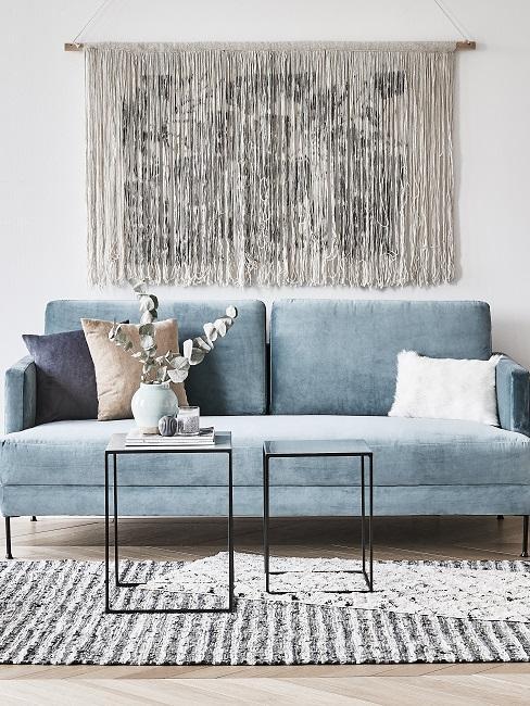 Sofá en azul pastel con decoración de pared con flecos en tono beige