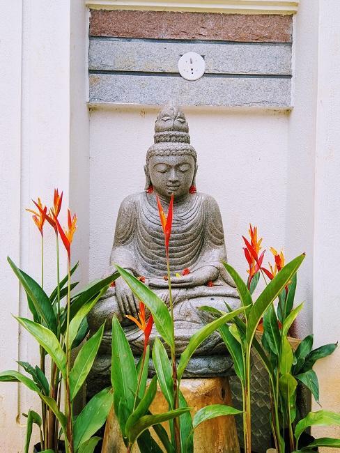 Grote Boeddha figuur op een houten kruk naast planten