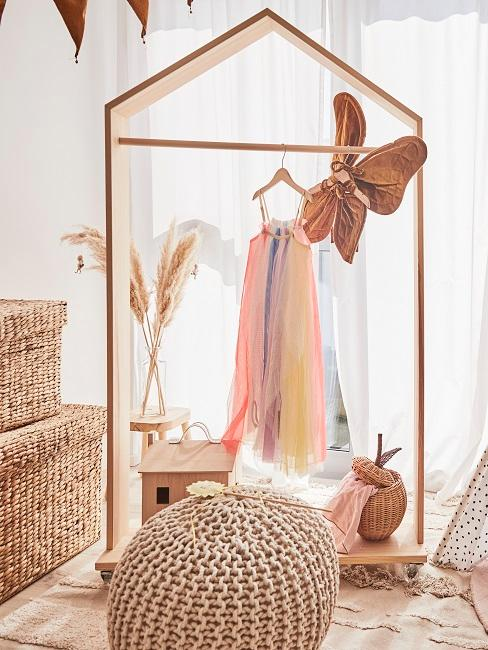 Kleiderständer aus Holz in einem Kinderzimmer, Pampasgras und Rattanboxen sowie ein Jute Pouf als Deko
