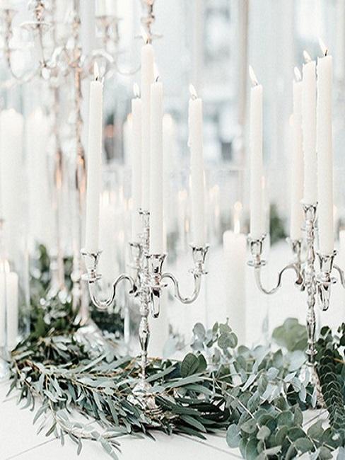Table de mariage decoree des feuilles d'eucalyptus, des chandeliers avec des chandelles blanches