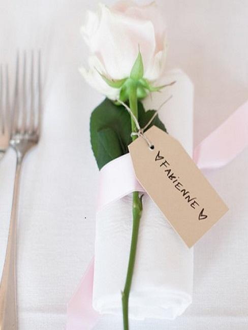 Serviette de table blanche décorée d'une rose blanche sur la table de mariage
