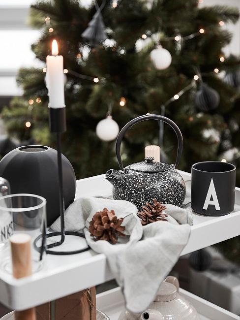Tablett vor einem Weihnachtsbaum mit einer Teekanne, einer Kerze, einer Tasse und Tannenzapfen als Deko
