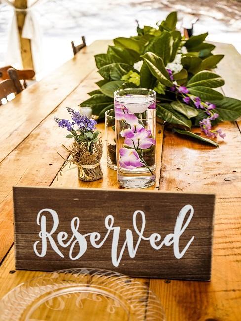 Langer Holztisch mit einem Schild und liegender Blumendeko in Kombination mit Blumen in der Vase und einem Töpfchen