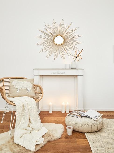 Weiße Kamin-Attrappe mit Kerzen neben Sessel mit Decke und Kissen