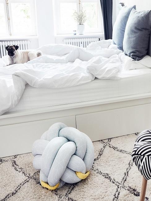 Kleines Schlafzimmer einrichten Deko Kissen in hellblau auf dem Boden