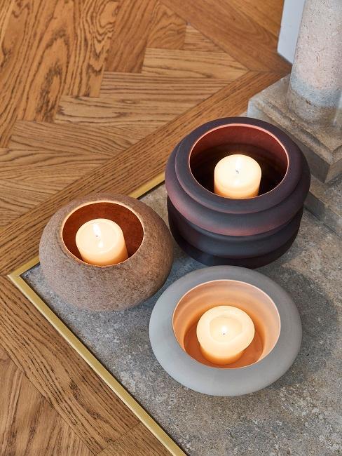 Drei Kerzenhalter mit Kerzem am Boden