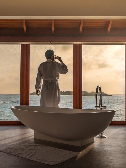 Ein Mann steht hinter einer freistehenden Badewanne und trink einen Kaffee.