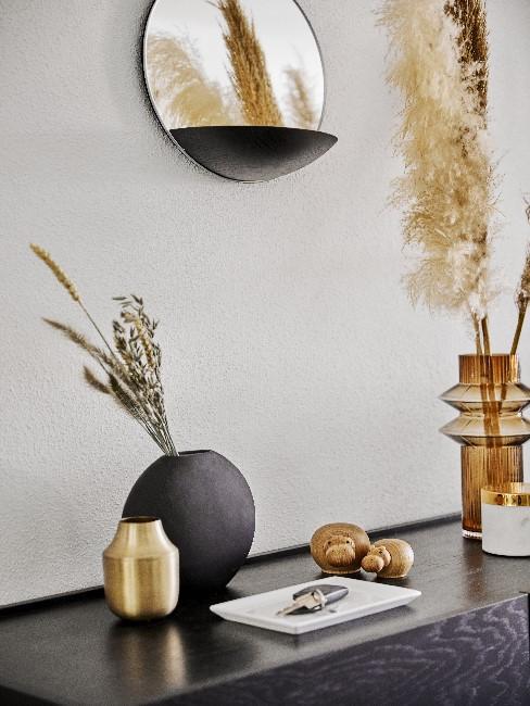 Schwarze Holz-Kommode mit Vasen in verschiedenen Farben und Gräsern