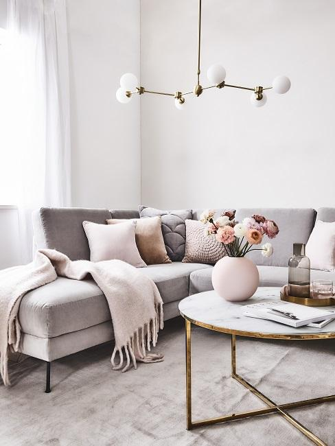 Luxus Wohnung einrichten Wohnzimmer Sofa mit vielen Kissen und Decke in hellrosa