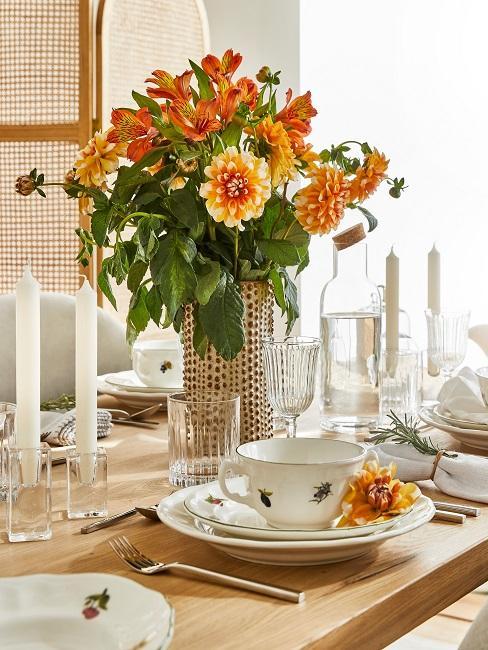 Frühlingshaft geschmückter Esstisch mit orangenen Blumen