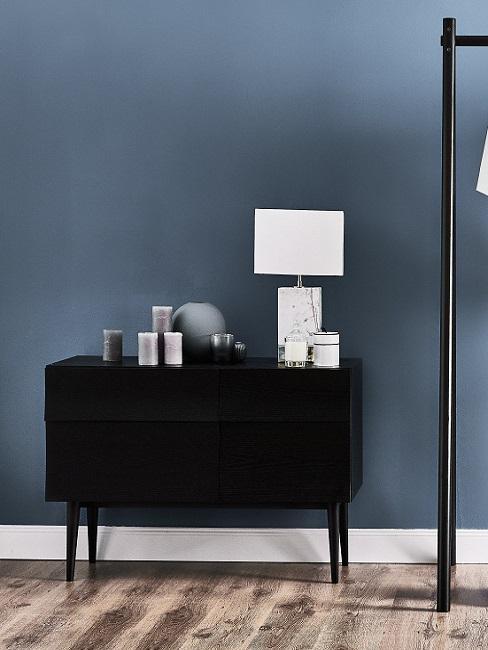 Designer Flur mit blauer Wand, schwarzem Sideboardund weißer Lampe