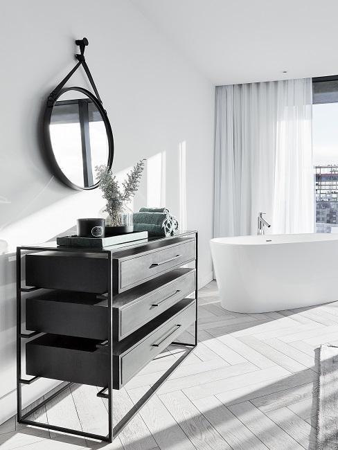 Designer Badezimmer in weiß mit freistehender Badewanne, rundem Wandspiegel und schwarzer Kommode