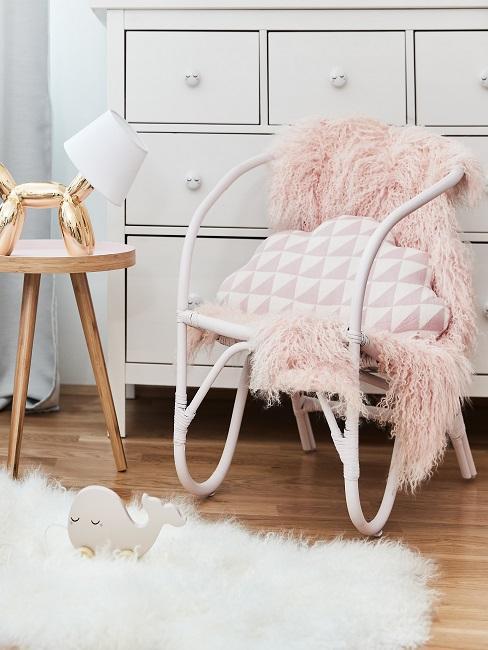 Weiße Kommode hinter einem Stuhl mit rosa Kissen und Fell, daneben ein Beistelltisch und als Teppich ein flauschiges Hochfloor-Modell