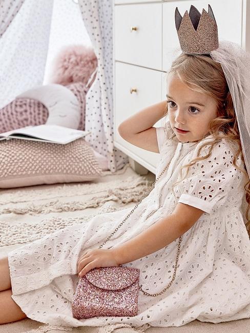 Ein Mädchen mit Krone und Glitzer Tasche sitzend in ihrem Luxus Kinderzimmer auf dem Teppich neben ihrem Luxus Tipi Spielzelt