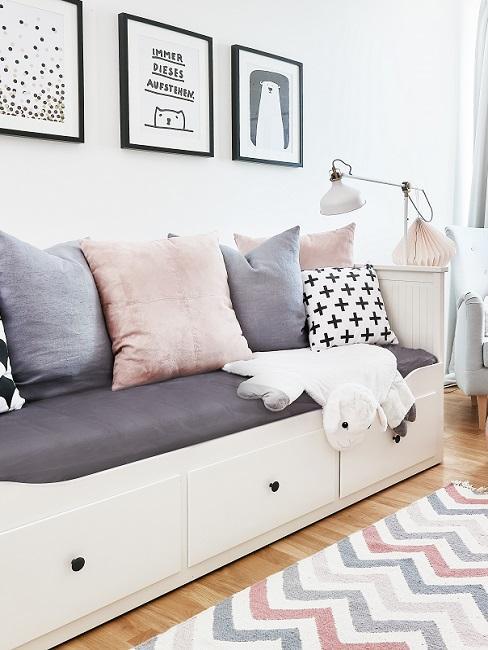Sofa mit Kissen in Kinderzimmer unter Bilderwand