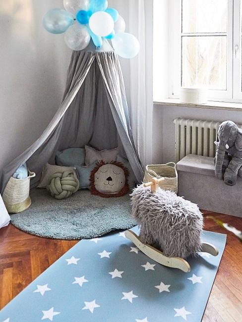 Babyzimmer in Grau und Blau mit Baldachin, Kissen und Spielteppich
