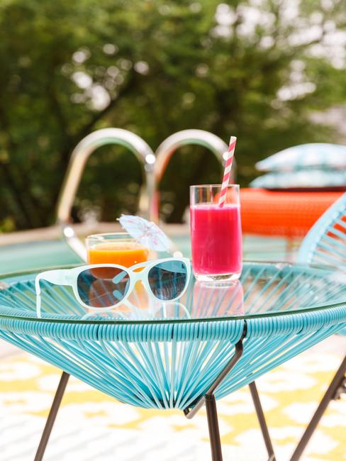 Mesa auxiliar de jardín con gafas de sol y cocktail estilo tropical