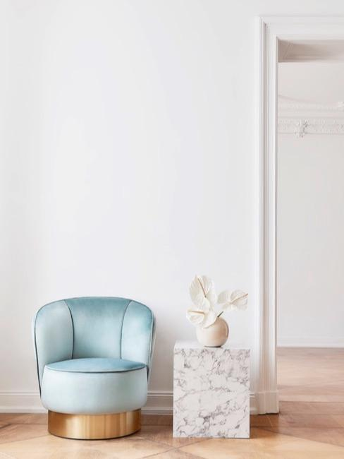 sillón de color turquesa, una mesa auxiliar veteada con un florero