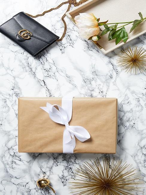 Regalo envuelto en papel marrón con lazo blanco sobre mesa de mármol junto a bolso de mano en cuero negro