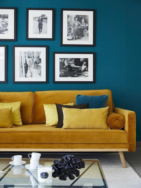Salón con pared azul con cuadros y sofá amarillo mostaza