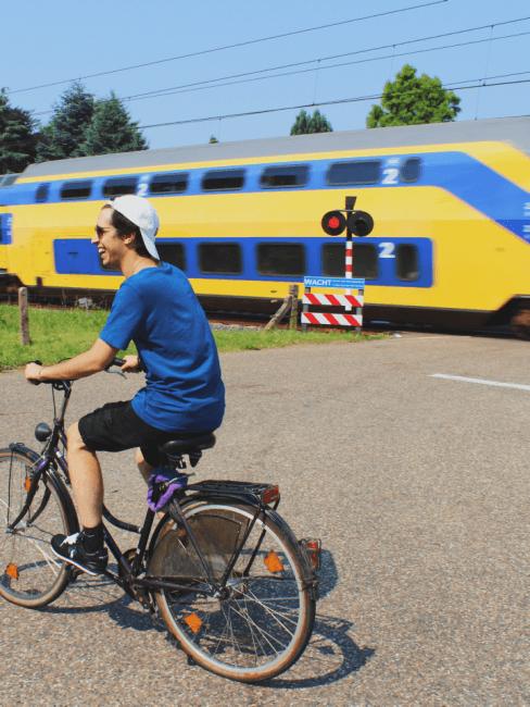 Chico en bici viajando y tren de fondo