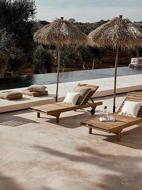 Terraza con piscina, chaise longues y sombrillas