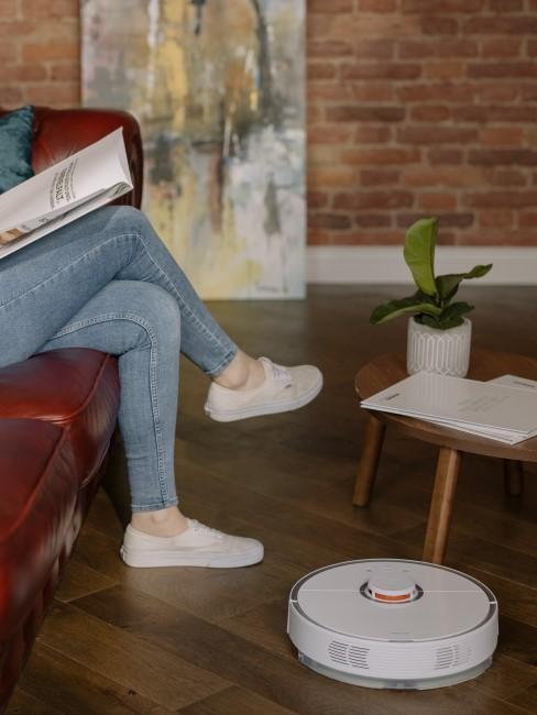 mujer leyendo mientras el robot de limpieza limpia