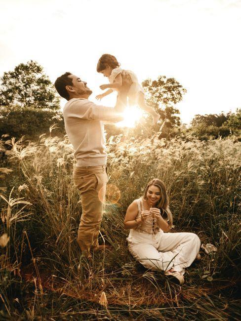 famille dans un pre, mama assise par terre, papa porte l enfant