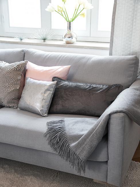 Canapé gris avec plaid et coussins en tons pastels